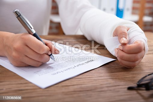 Close-up Of Businesswoman With White Bandage Hand Filling Work Injury Claim Form On Wooden Desk