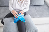 Injured woman holding ice pack / bag for cooling down the knee pain.