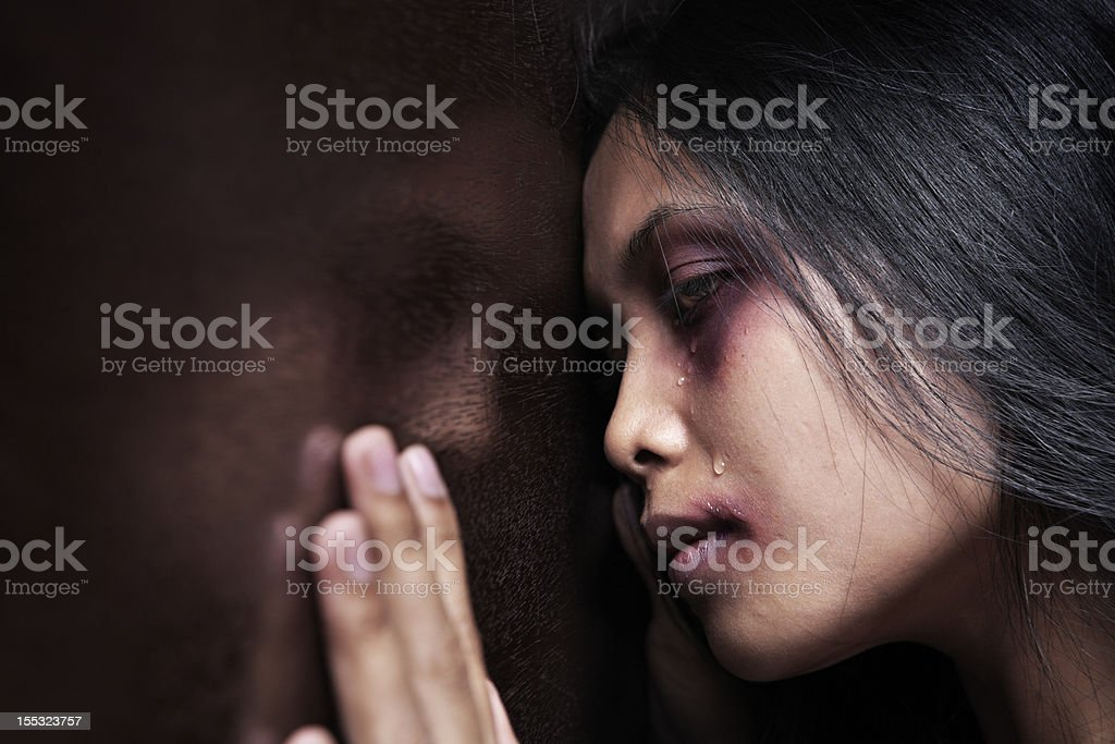 Injured woman leaning sadly on wooden wall stock photo