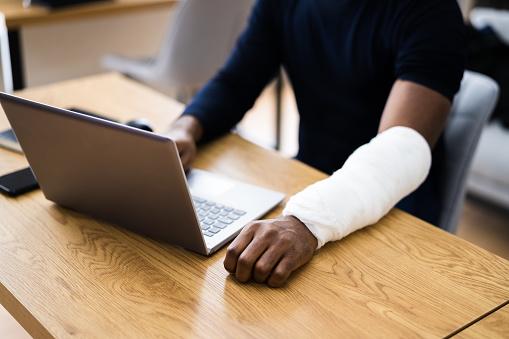 Injured Worker Compensation. Broken Arm African Man On Computer