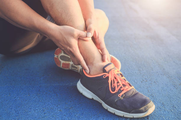 injury from workout concept : asian man use hands hold on his ankle while running on road in the park. focus on ankle. - caviglia foto e immagini stock