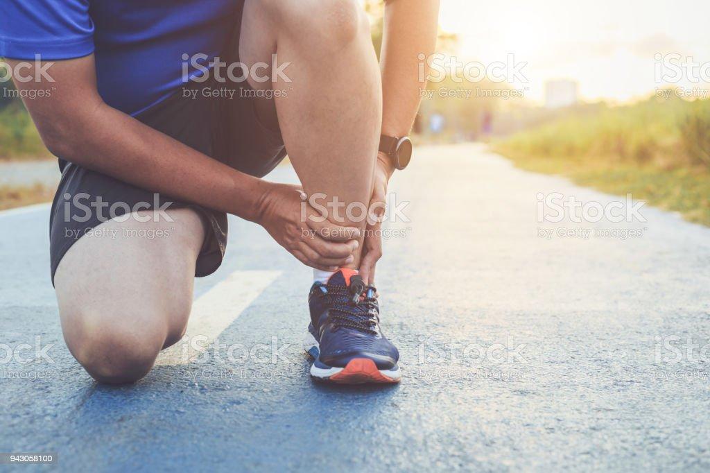 Verletzungen durch Training Konzept: asiatischer Mann Gebrauch Hände halten an seinem Knöchel beim laufen im Park unterwegs. Konzentrieren Sie sich auf die Knöchel. - Lizenzfrei Arthrosen Stock-Foto