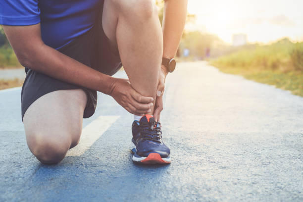 injury from workout concept : asian man use hands hold on his ankle while running on road in the park. focus on ankle. - slogatura foto e immagini stock