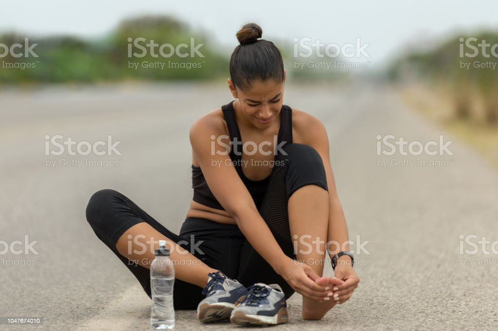 Injury her foot on road stock photo