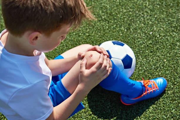 Blessure du genou dans le football garçon - Photo