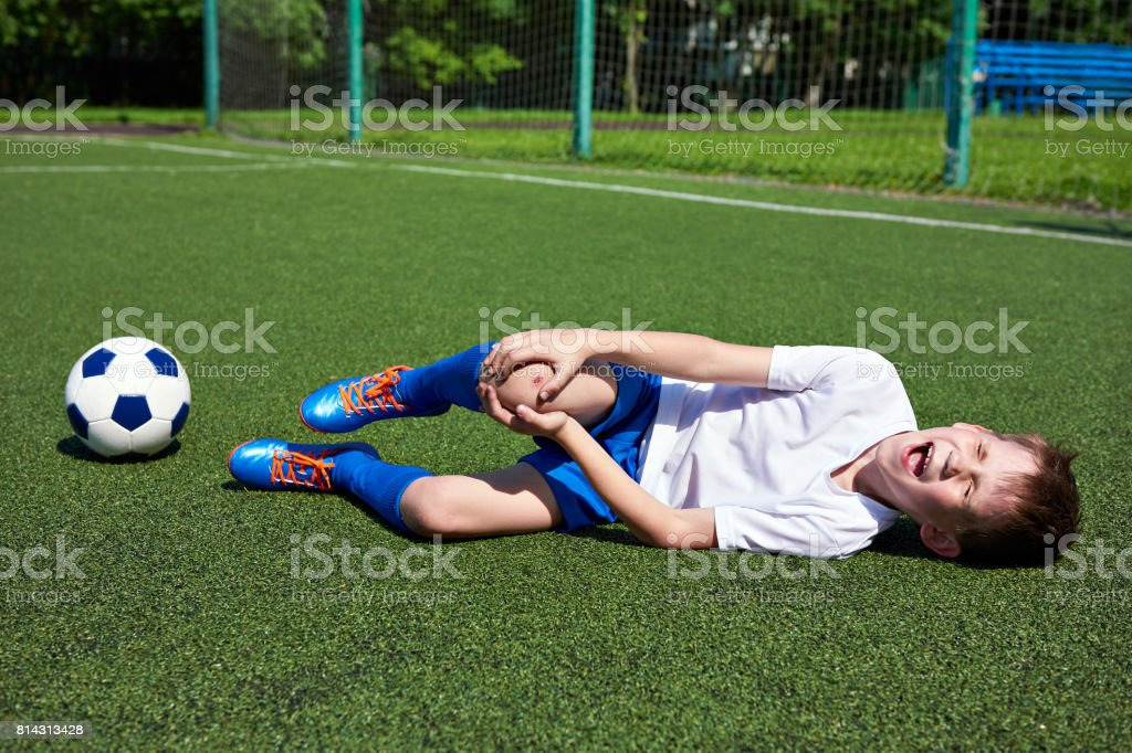 Injury of knee in boy football stock photo