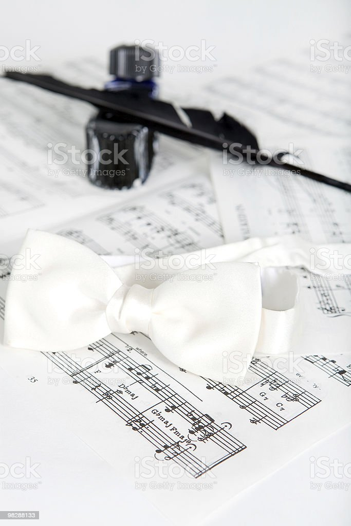Ink bottle, feather, bow-tie and notes royalty-free stock photo
