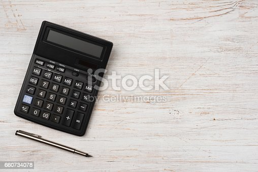 istock Ink pen and black calculator isolated on wooden texture background 660734078