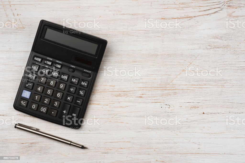 Ink pen and black calculator isolated on wooden texture background stock photo