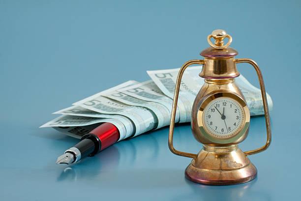 tinte stift, geld und zeit auf blauem hintergrund - sinn uhren stock-fotos und bilder