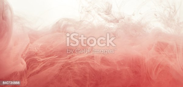 Ink swirl in water isolated on white background. The paint in the water. Soft dissemination a droplets of pink ink in water close-up. Abstract background. Explosion of splashes yellow acrylic ink.