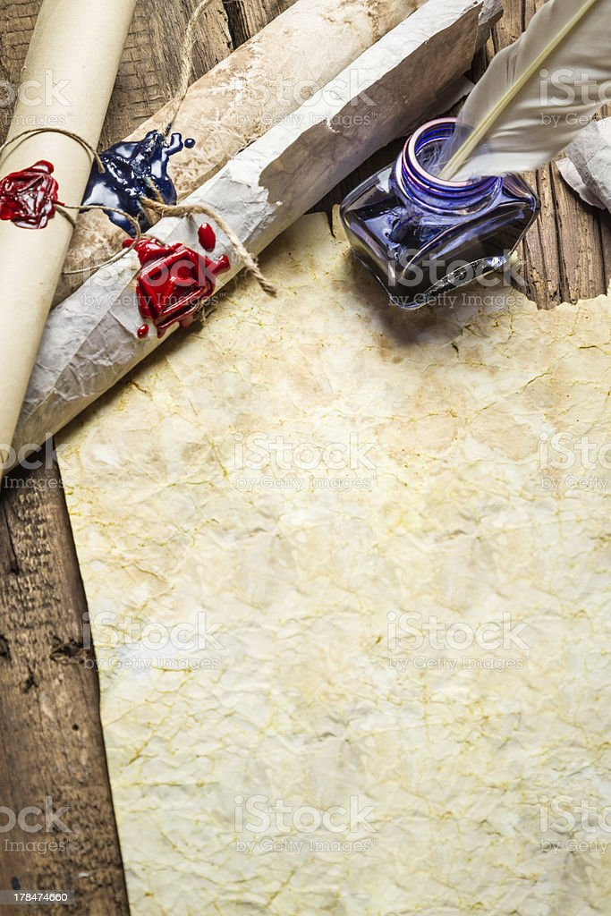 Inkwell and ancient scrolls on old sheet of paper stock photo