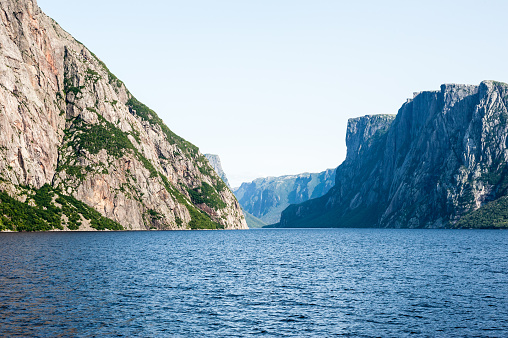 Inland fjord between large rugged steep cliffs with some green vegetation on rock face, at Western Brook Pond, Gros Morne National Park, Newfoundland, Canada.