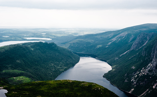Inland fjord flowing between large steep cliffs, with green landscape disappearing into clouds and fog, at top of Gros Morne Mountain, Gros Morne National Park, Newfoundland, Canada.