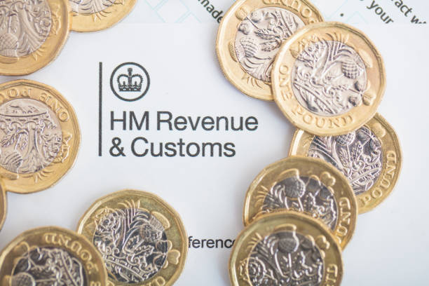 UK Inland Revenue Tax Form An editorial stock photo of the UK Inland Revenue Tax forms with the new 2017 One Pound Coins. income tax stock pictures, royalty-free photos & images