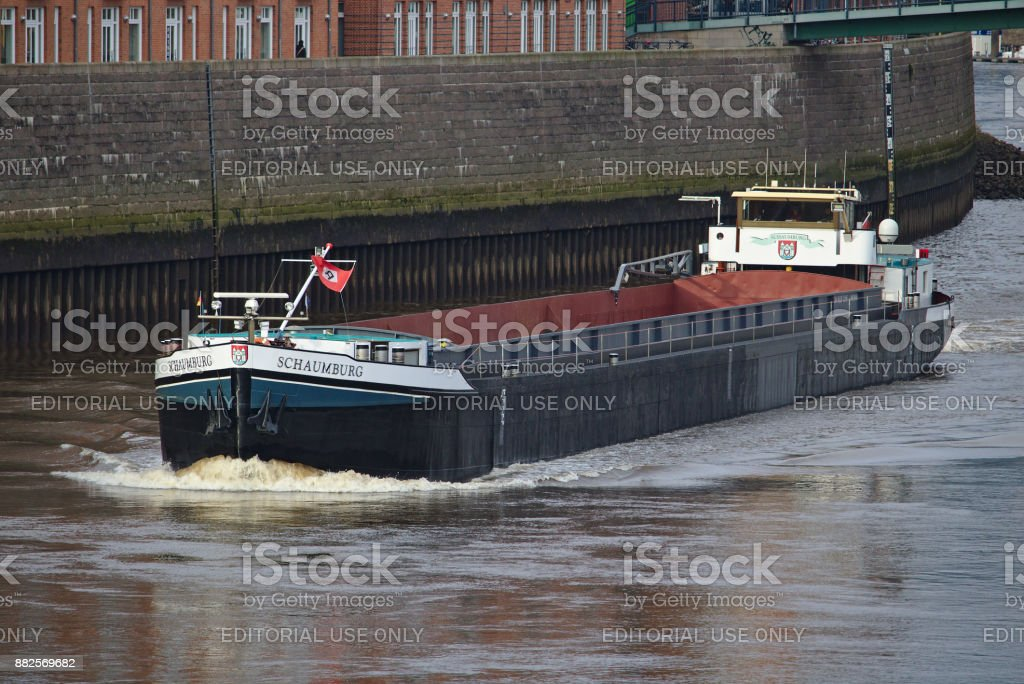 Inland vessel on the river weser with stone pier in the background stock photo