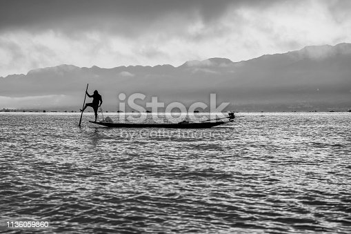 Full frame shots of Inle lake fisherman fishing with one foot while standing  on the boat