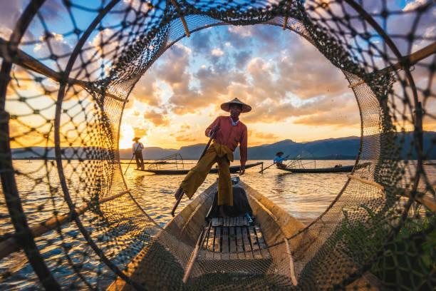 Inle Lake Intha Fishermen at Sunset in Myanmar (Burma) Inle Lake Intha fishermen at sunset in Myanmar (Burma). myanmar stock pictures, royalty-free photos & images