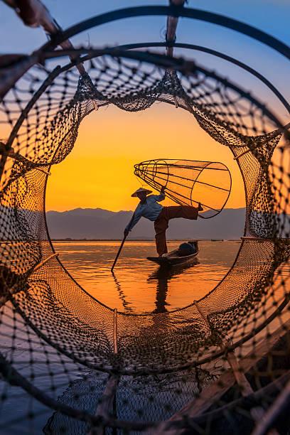Inle lake Myanmar Fishermen sihouettes at Inle lake on sunset, Myanmar myanmar stock pictures, royalty-free photos & images