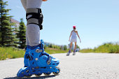 two people rollerblade on the street in the summer