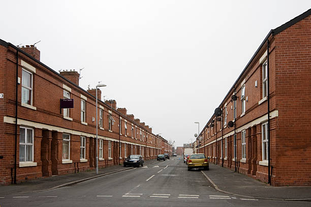 Inner city housing Street of row houses / terraced houses in an inner city area. This is Moss Side, Manchester, UK. northwest england stock pictures, royalty-free photos & images