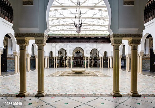 The peristyle of the Great Mosque of Paris borders a courtyard with a circular ablutions basin in the center.