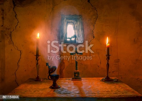 inner sanctuary of a chapel with burning candles, the flame of censer and the holy cross. The eastern wall aged over a century in the background.