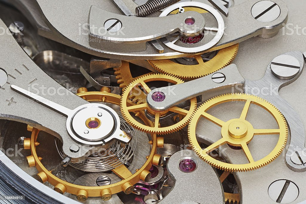 Inner workings of a clock with silver and gold instruments stock photo