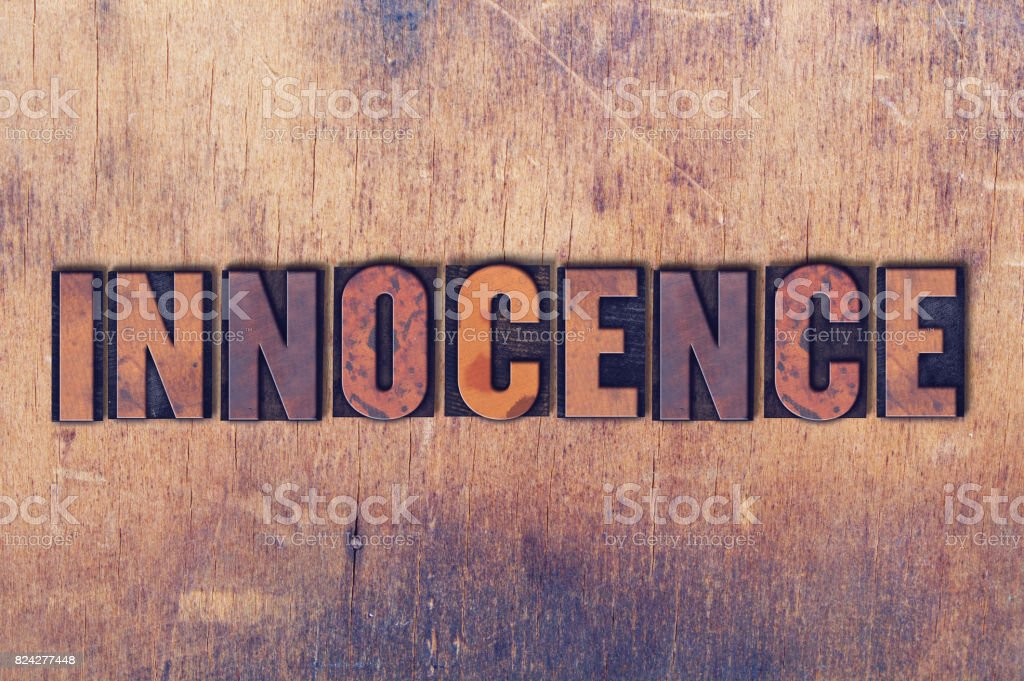 Innocence Theme Letterpress Word on Wood Background stock photo