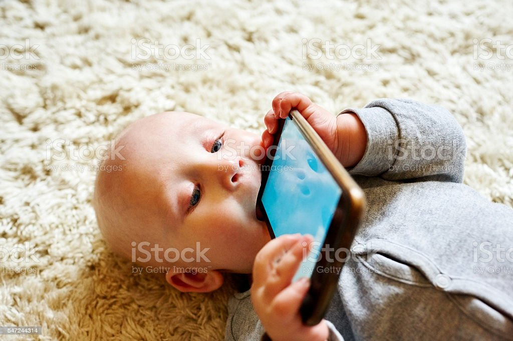 Innocent baby boy chewing a cellphone stock photo