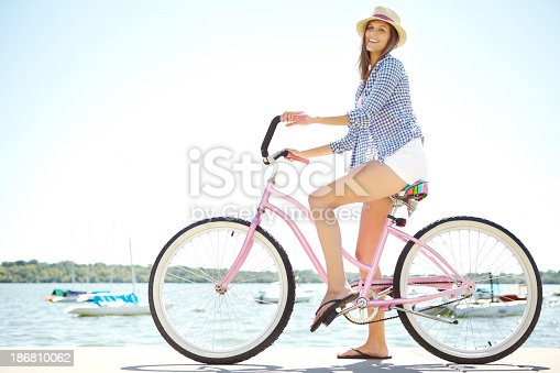 A happy young woman riding her bike at the waterfront