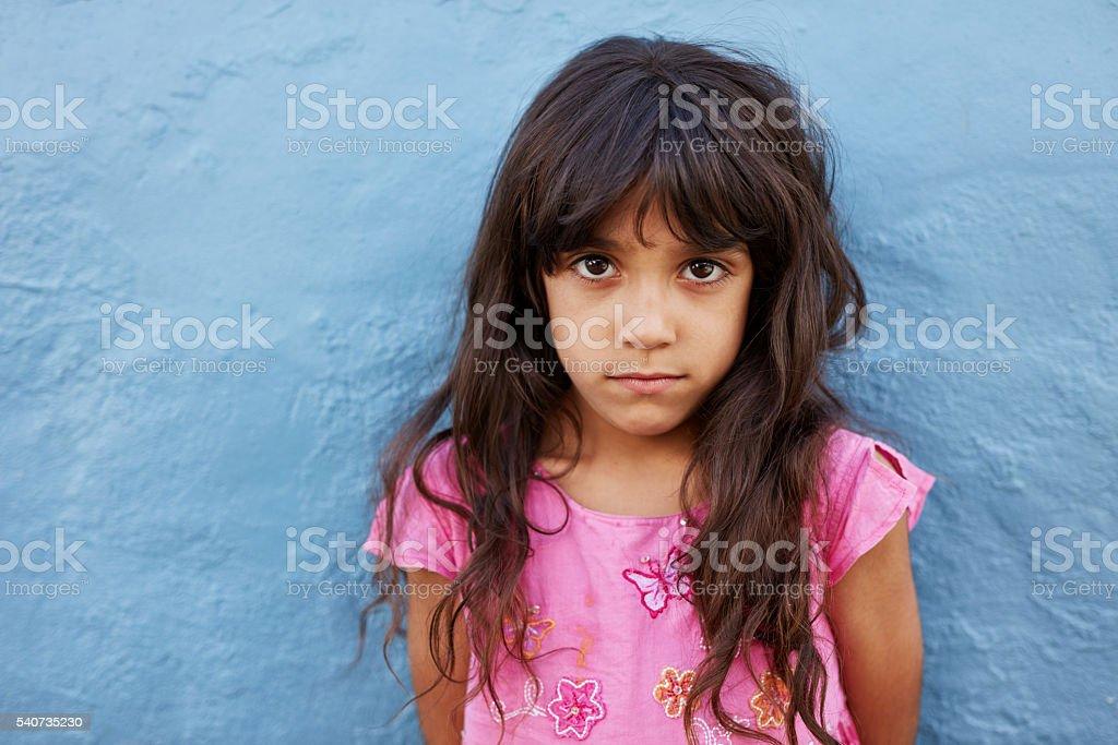 Innocent little girl standing against blue wall stock photo