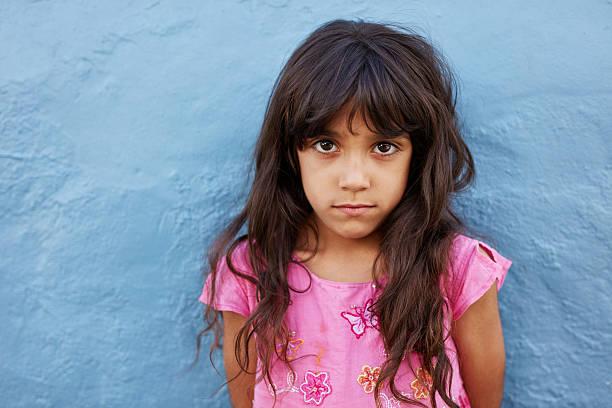 innocent little girl standing against blue wall - starren stock-fotos und bilder