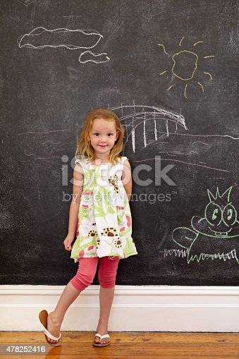 istock Innocent little girl standing with chalk drawings at home 478252416