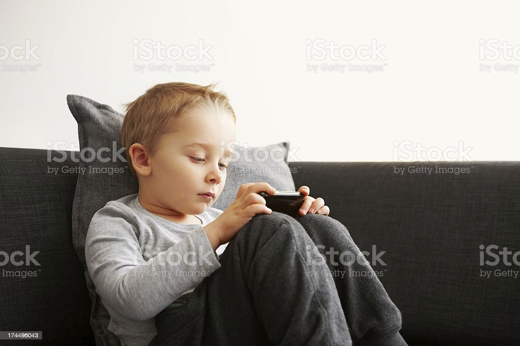 Innocent little kid using mobile phone stock photo