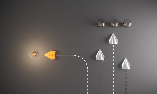 Group of paper airplane in one direction and with one individual pointing in the different way to the glowing lightbulb, can be used leadership/individuality/innovation concepts.( 3d render )