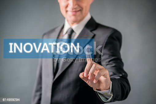 Touch screen concept in studio , Businessman is Press a Button , Finger Pointing at Innovation virtual word against black background