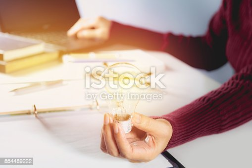 istock Innovation or creative concept of hand hold a light bulb with laptop. 854489222