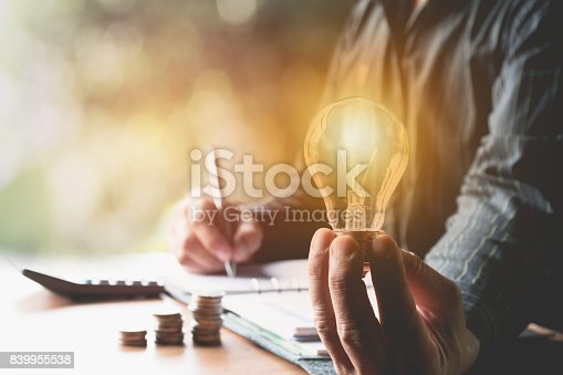 istock Innovation or creative concept of hand hold a light bulb with calculator. 839955538