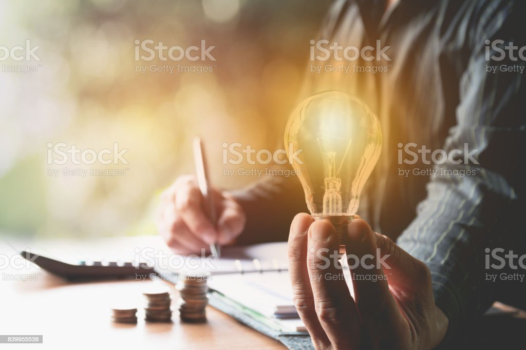 Innovation or creative concept of hand hold a light bulb with calculator. stock photo