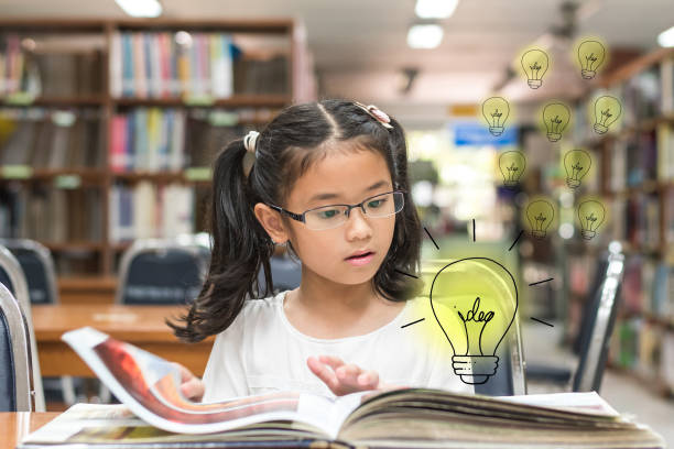 innovatieve creatief idee voor auteursrechten wet concept met kid verrast lezen boek met gloeilamp in bibliotheek - a little girl reading a book stockfoto's en -beelden