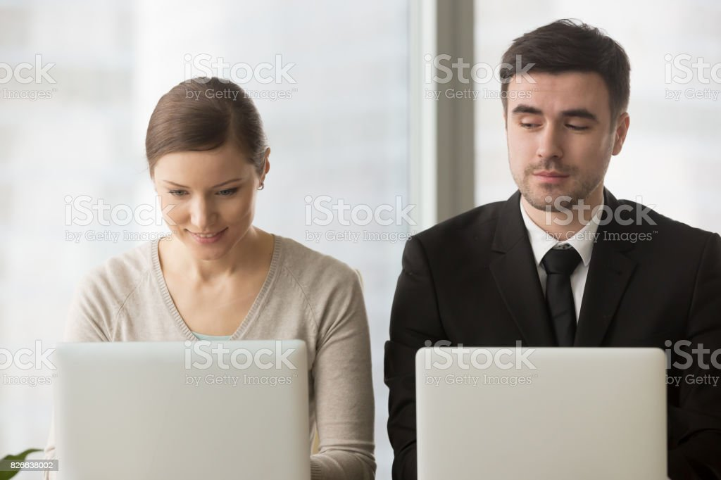 Inquisitive competitor sneakily stealing idea, copying work from rival laptop stock photo