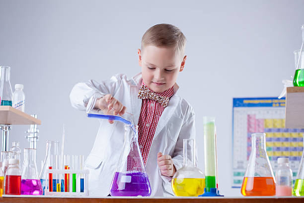 inquisitive naturalist mixes reagents in flask - young nudist boys stock photos and pictures