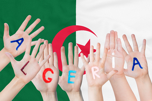 Inscription Algeria on the children's hands against the background of a waving flag of the Algeria
