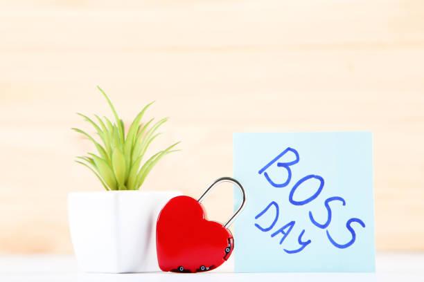 día del jefe de la inscripción, planta verde y candado en forma de corazón sobre fondo de madera - boss's day fotografías e imágenes de stock