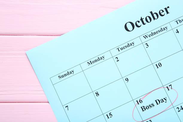 inscripción jefe día en calendario sobre mesa de madera - bosses day fotografías e imágenes de stock