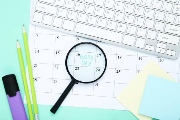 día del jefe de inscripción en el calendario con lupa y teclado sobre fondo azul - boss's day fotografías e imágenes de stock