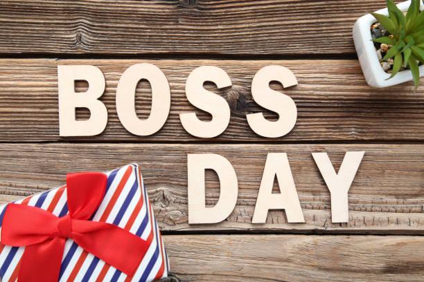 inscripción jefe día con caja de regalo y planta verde en la mesa de madera - boss's day fotografías e imágenes de stock