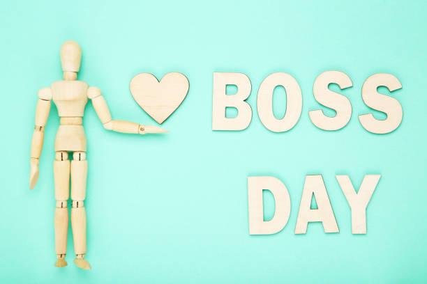 día del jefe de la inscripción con figura de madera sobre fondo azul - boss's day fotografías e imágenes de stock