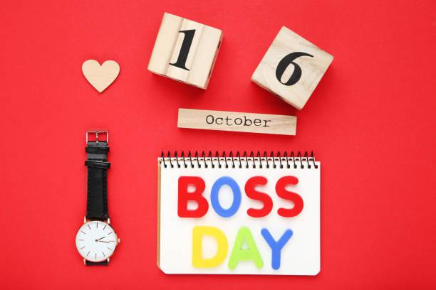día del jefe de la inscripción con reloj de pulsera y calendario de madera sobre fondo rojo - boss's day fotografías e imágenes de stock